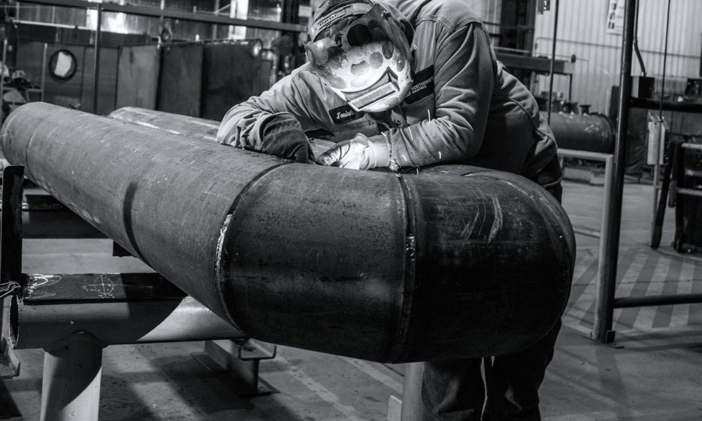 Person welding large pipe