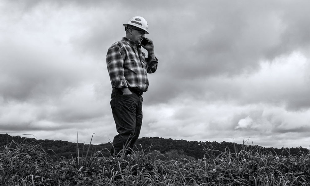 Man wearing hardhat talking on cell phone while standing in a field